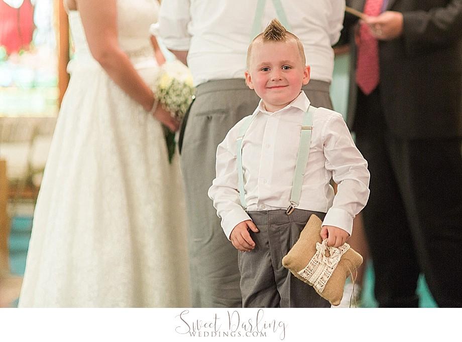 ring bearer in suspenders and carrying burlap pillow