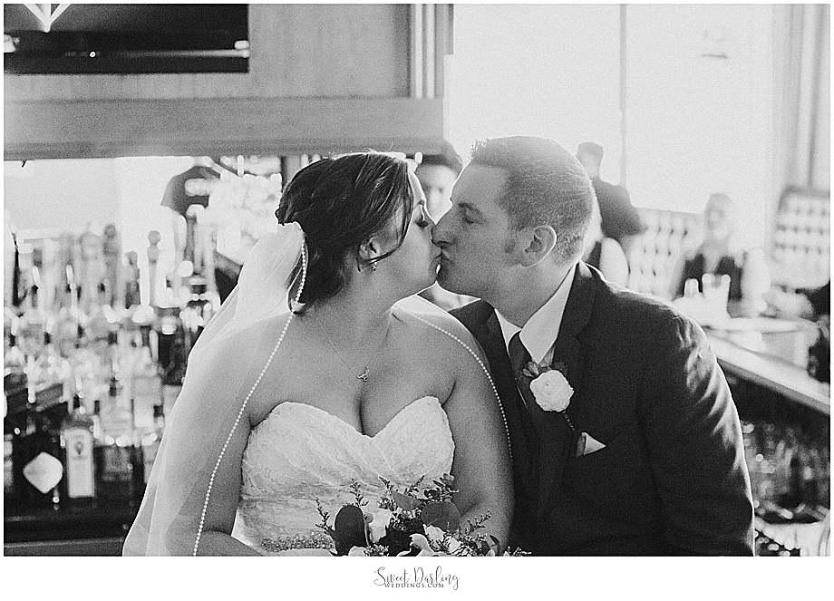 bride and groom kissing at guidos bar