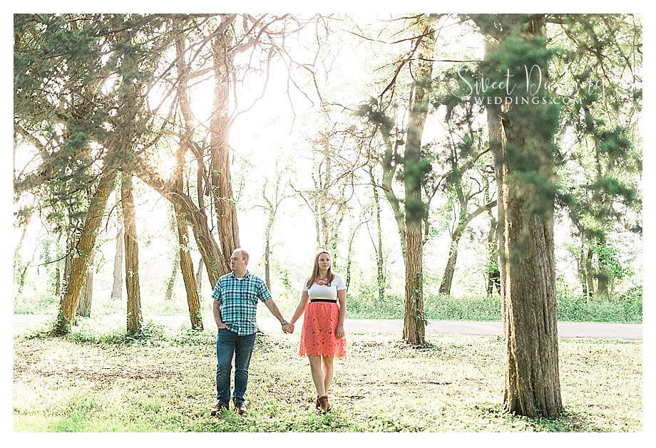 Golden light with couple standing among trees