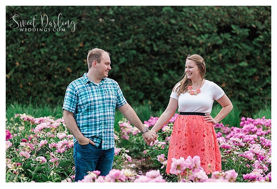 Engaged couple in red pink peonies garden Allerton