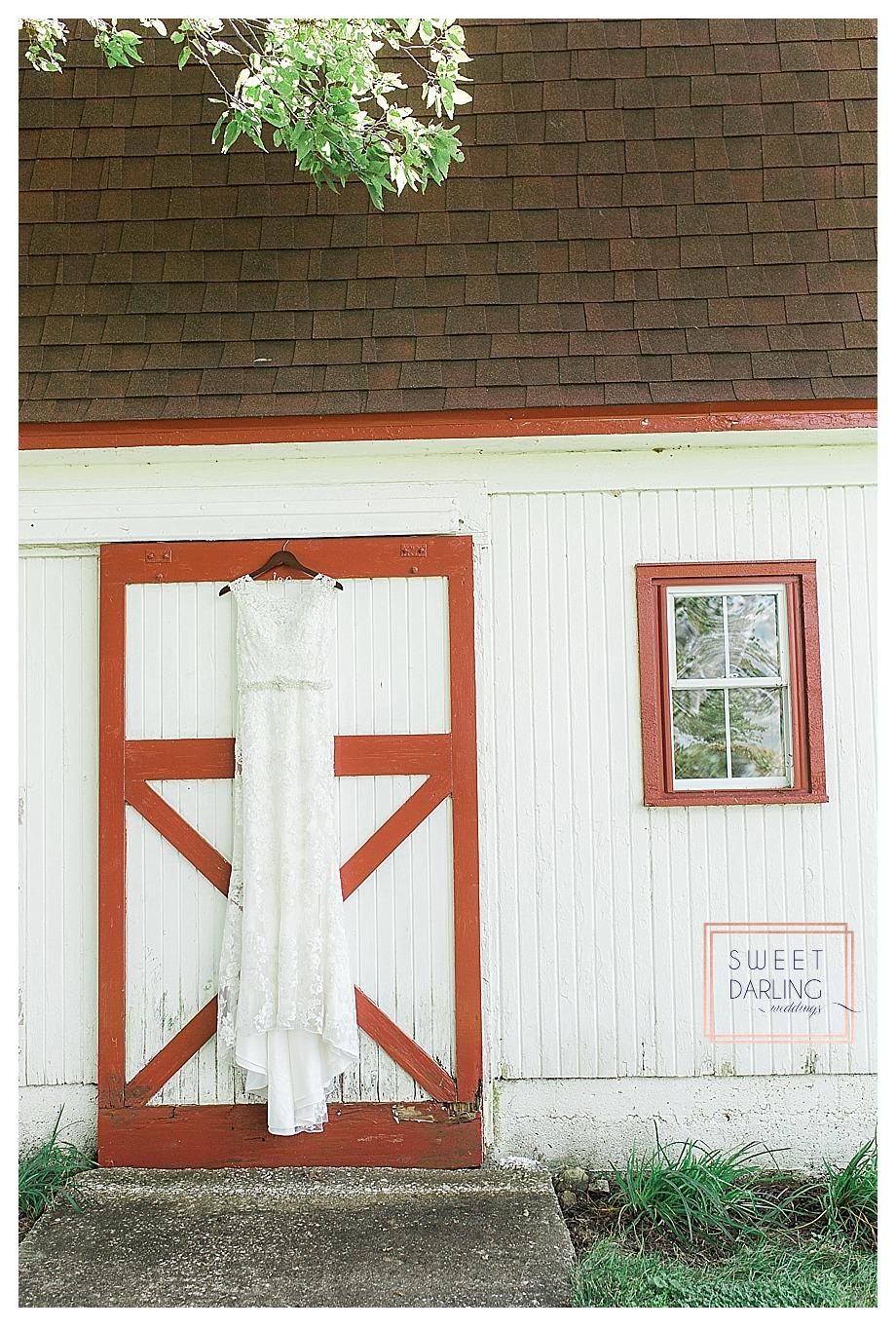 white lace slip dress hanging on barn