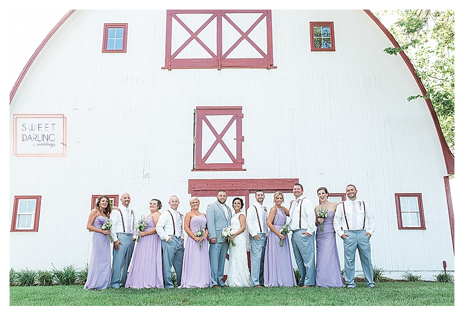 wedding with purple lavender dresses in front of barn
