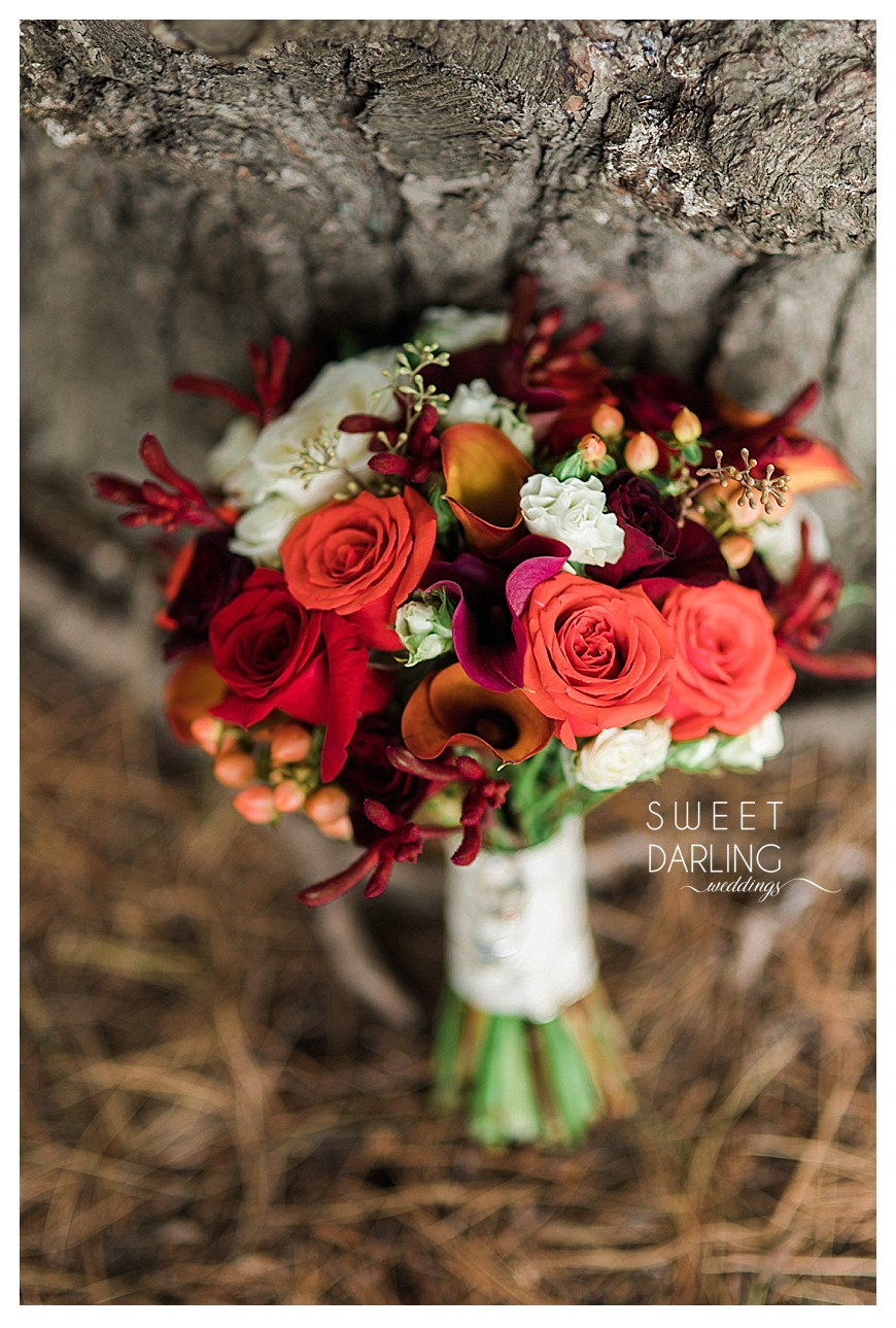 wedding bouquet of red roses, spray painted soybeans orange calla lillies burgundy purple yellow flowers