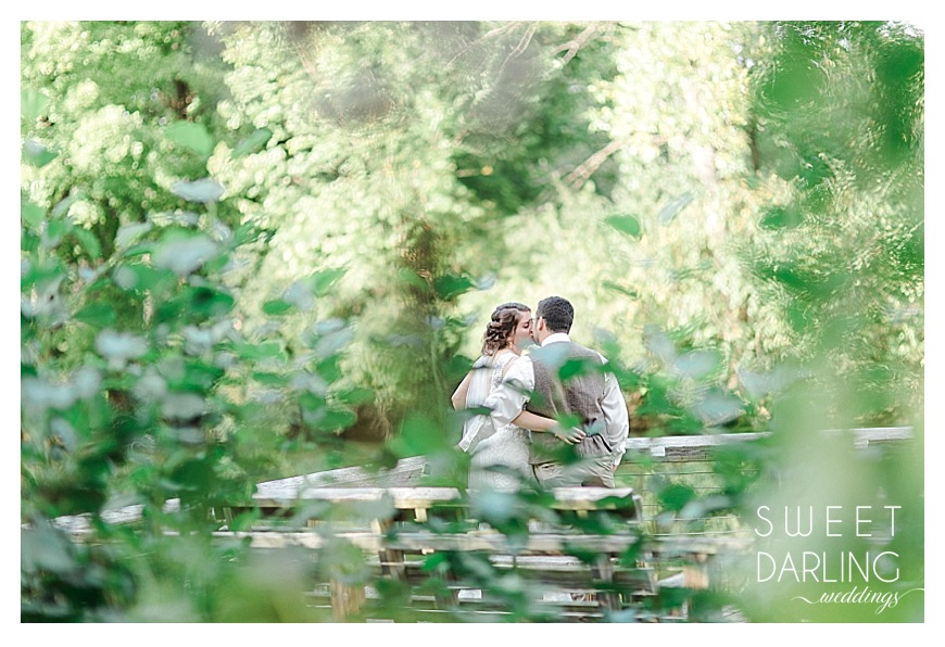 kissing bride and groom on the dock of a river