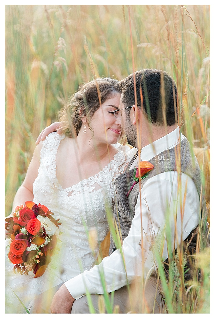 bride and groom photo in tall grass outdoors kissing