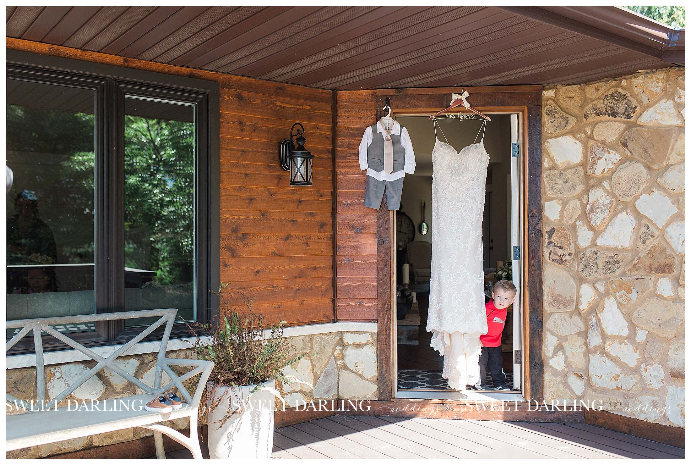 Bride's dress hanging with ring bearer's outfit