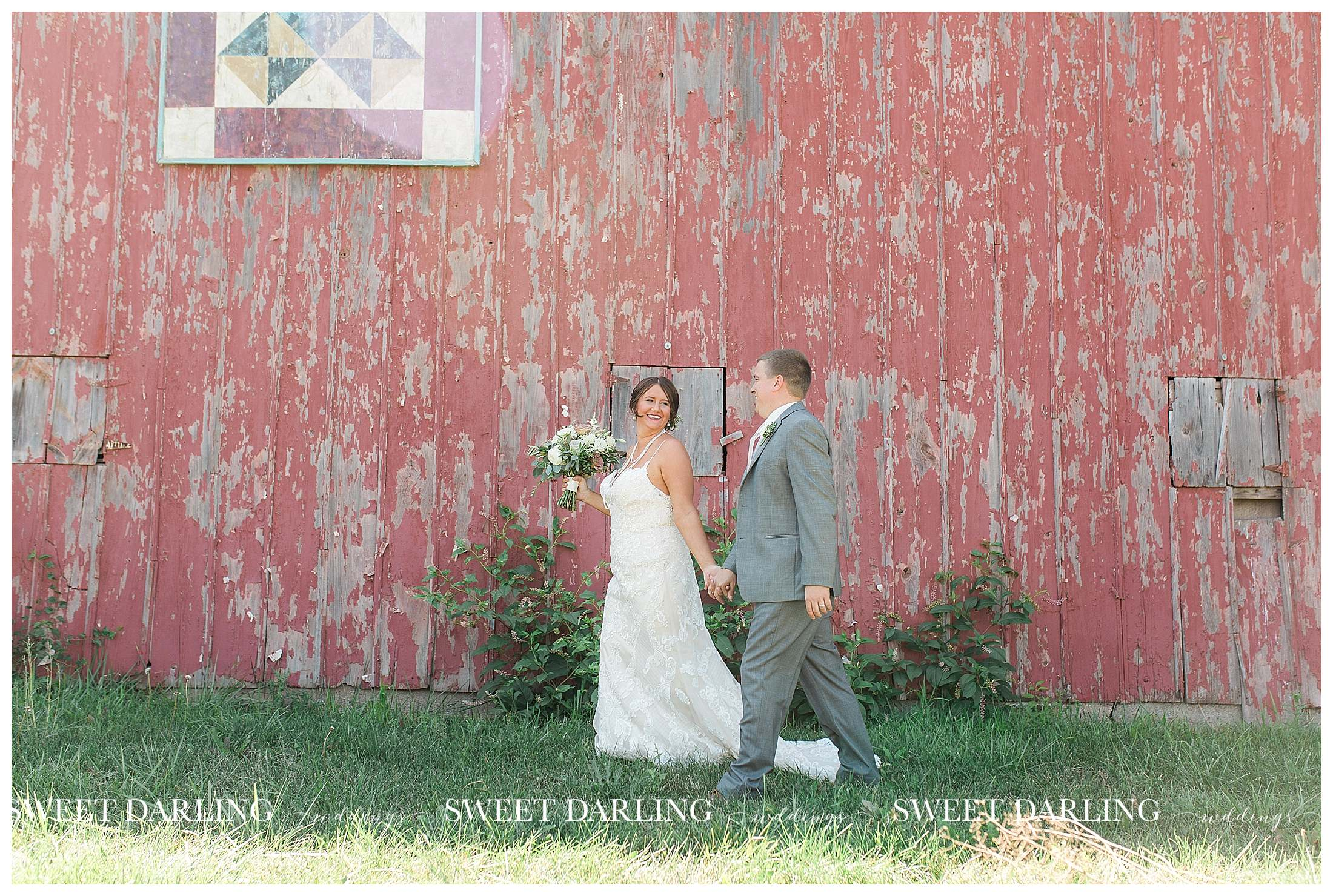 Bride and groom walking at red barn in Champaign, IL