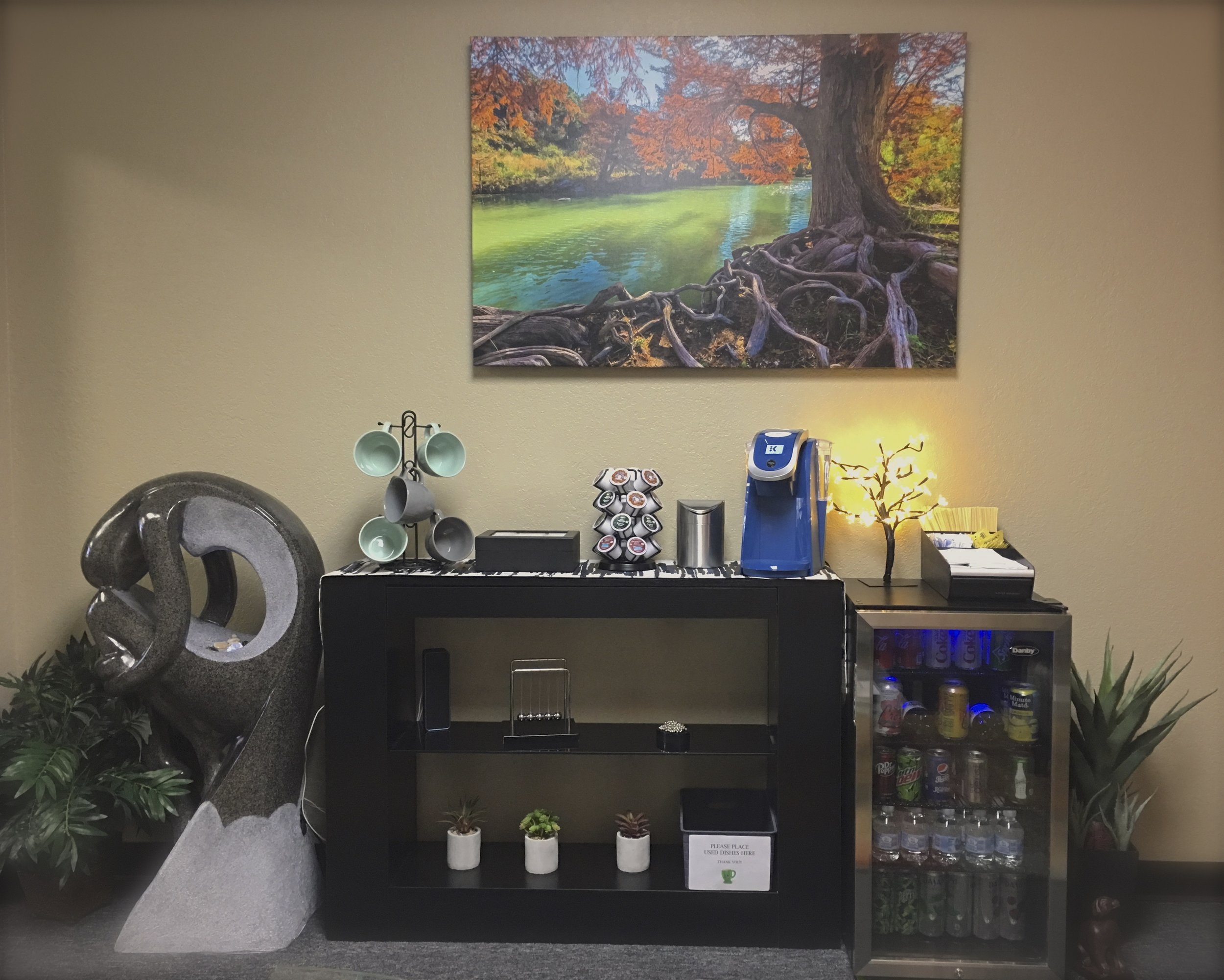 The FCS reception area features a complimentary beverage center stocked with soda, coffee, tea, and water.