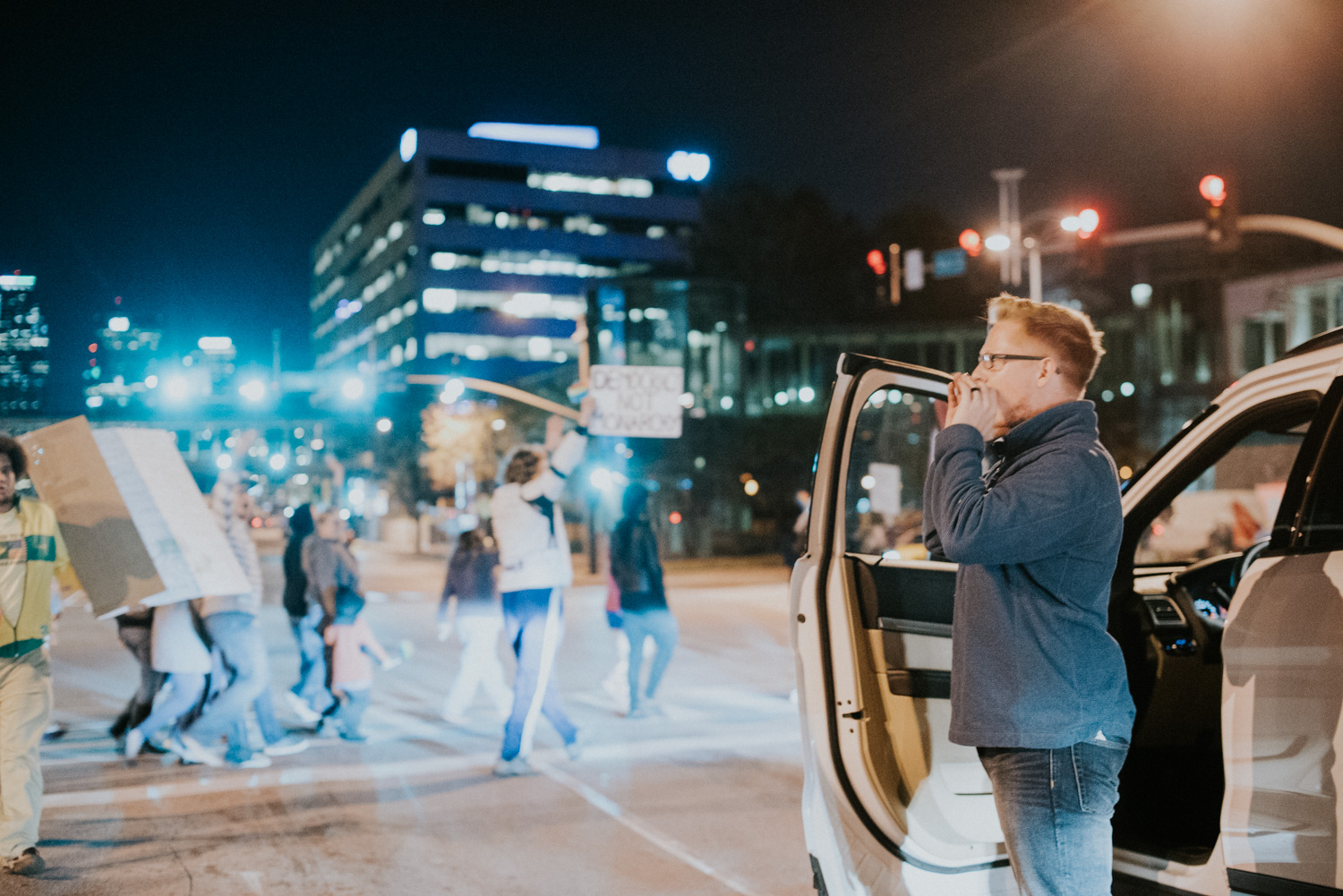 A man hops out of his car in support for the Love Trumps Hate protesters as they cross an intersection in downtown Kansas City.