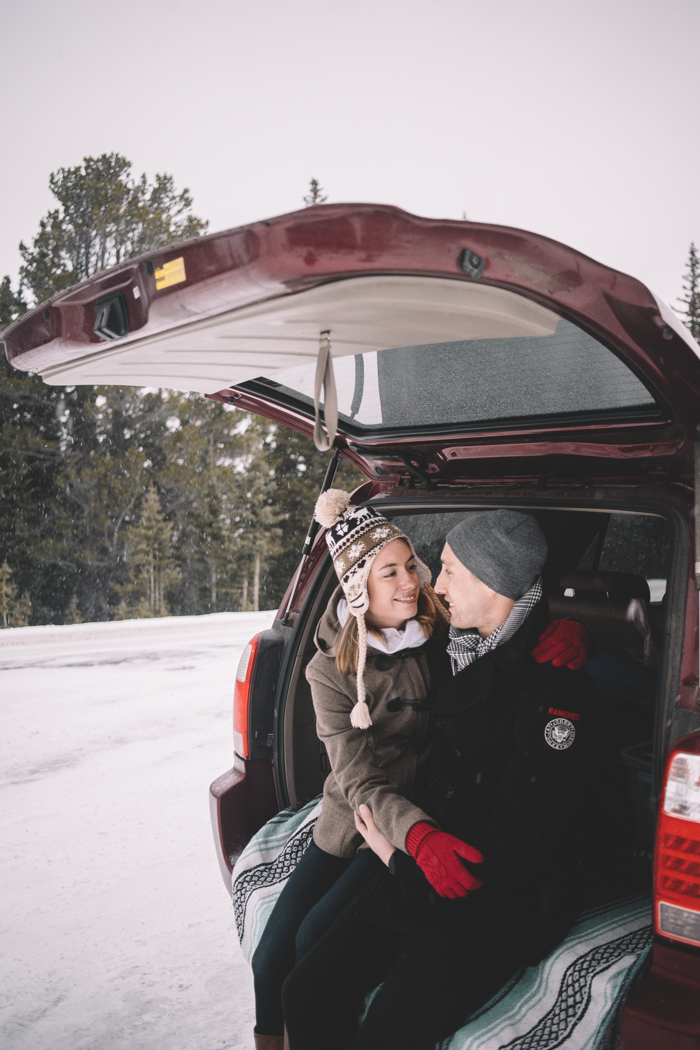 Back of Car Snowing Engagement in Mountain Town, Colorado