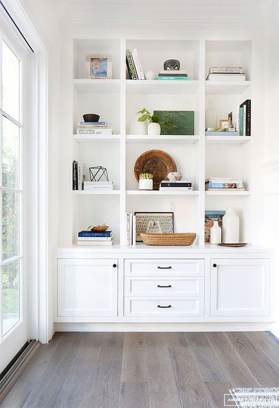 Gorgeous white custom bookshelves and styling by  Amber Interiors .