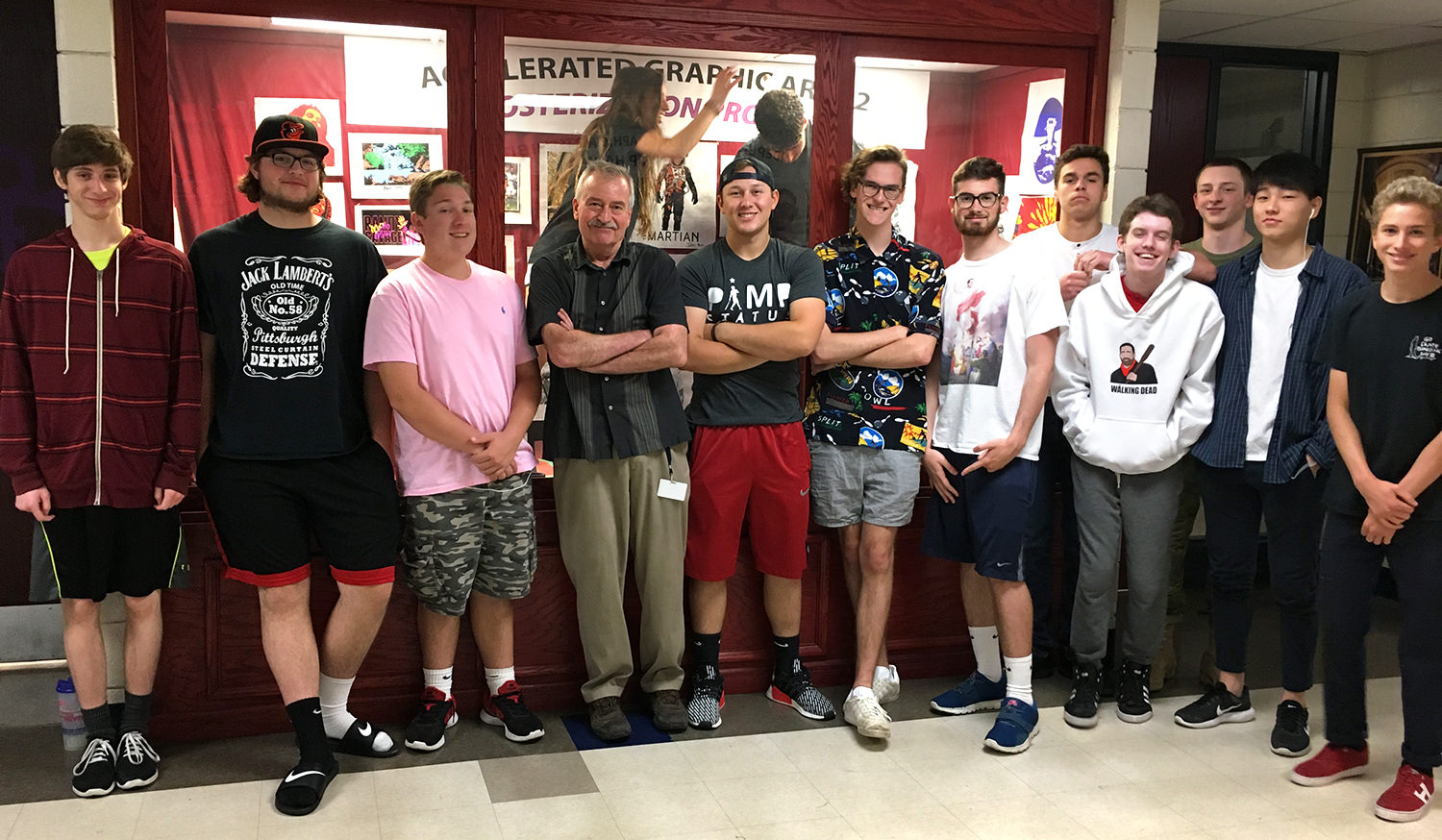 Mr. Inlander (Don) and his Accelerated Graphic Arts II students. Two students are in the glass case behind him, installing artwork.