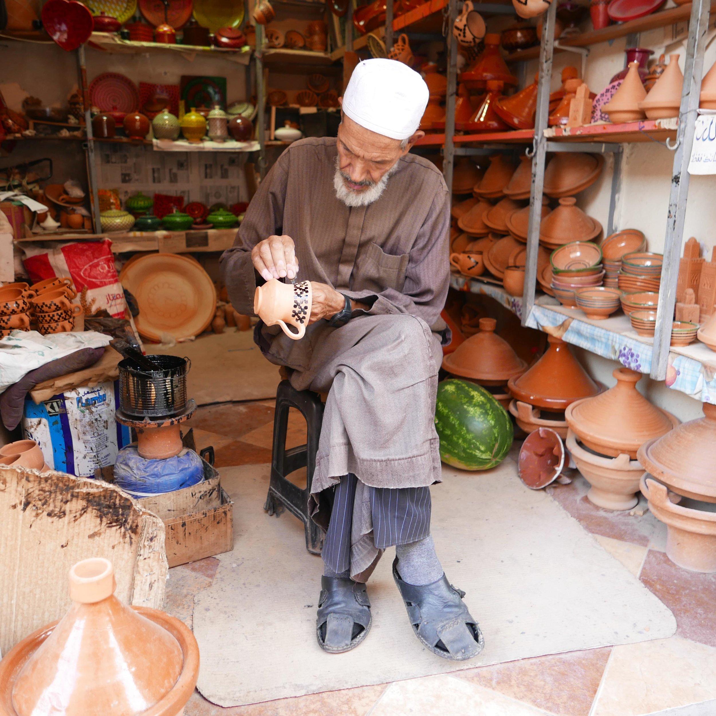 Datcha - Artisan marocain spécialisé dans le décor de céramiques à l'huile de cade dans son atelier