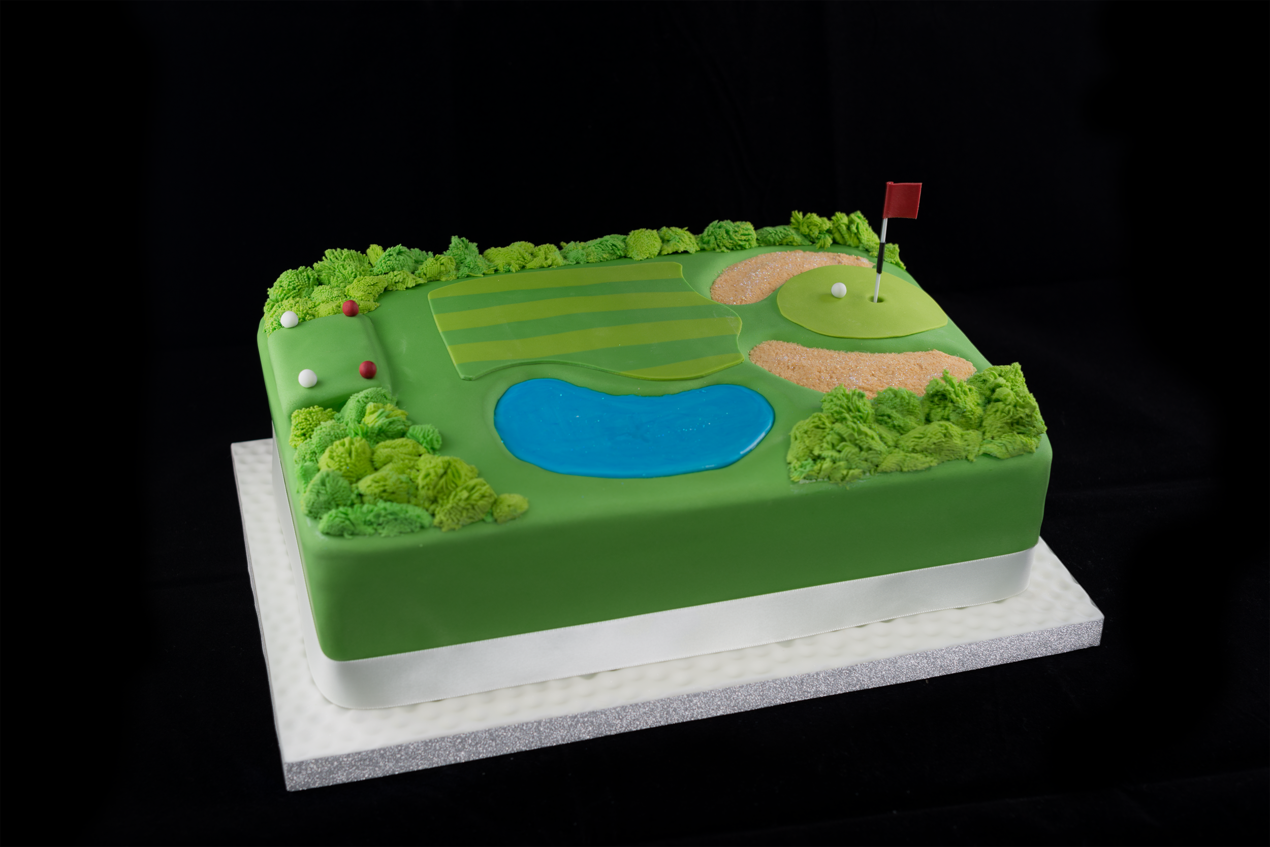 Vanilla sponge on the inside, shortbread bunkers on top. All decorated with individually made 'rough' around the outside and a flood icing water hazard.