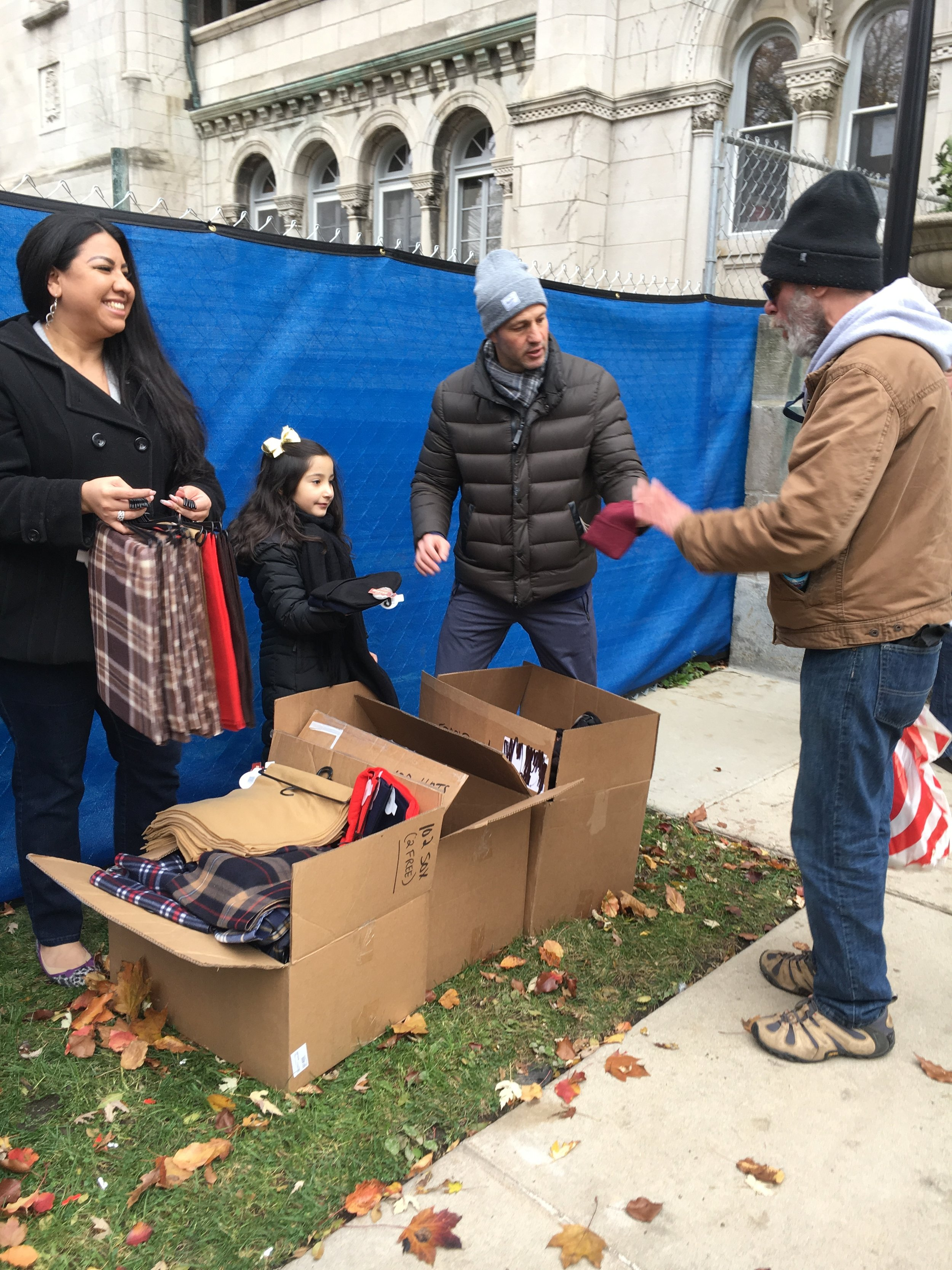 Tim Whiting and other volunteers handing out gloves, scarves and socks.