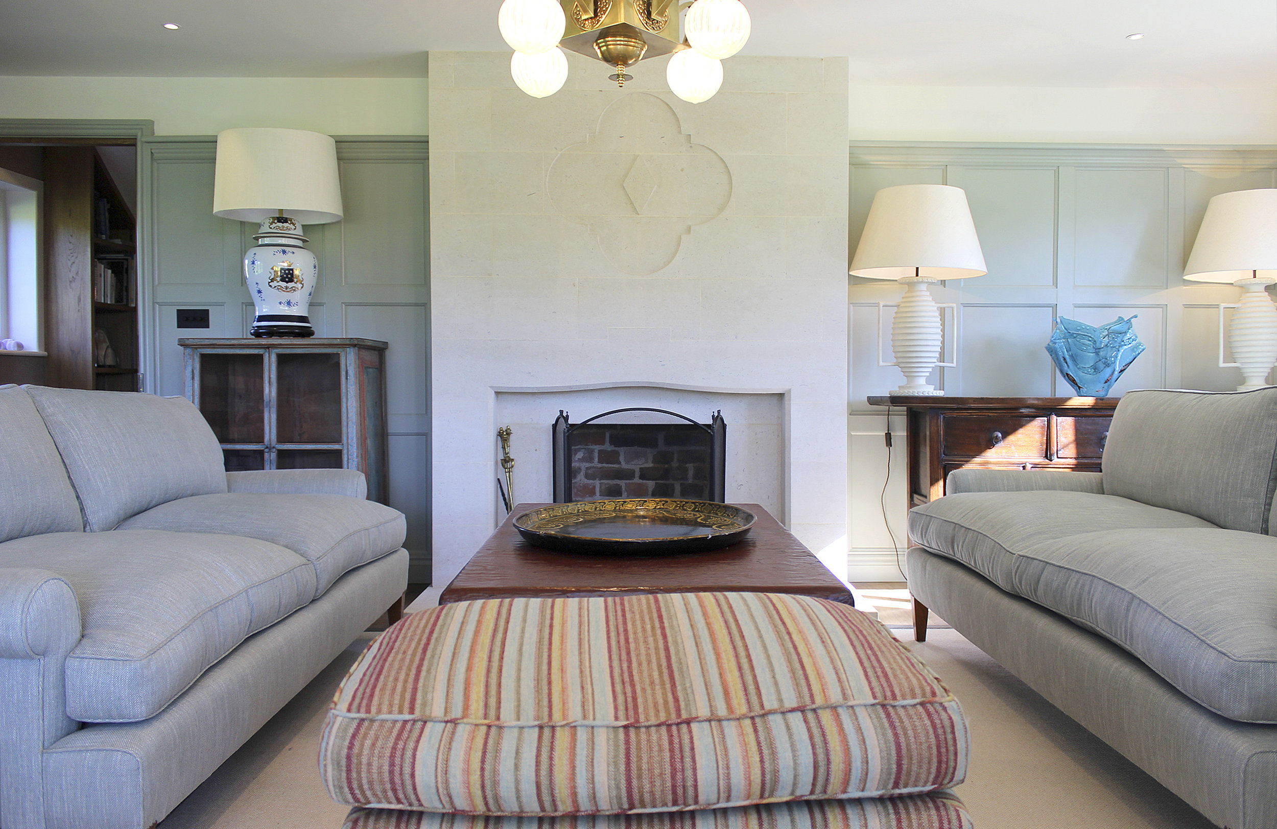 Drawing room area, with bespoke sandstone fireplace and handmade wooden panelling.
