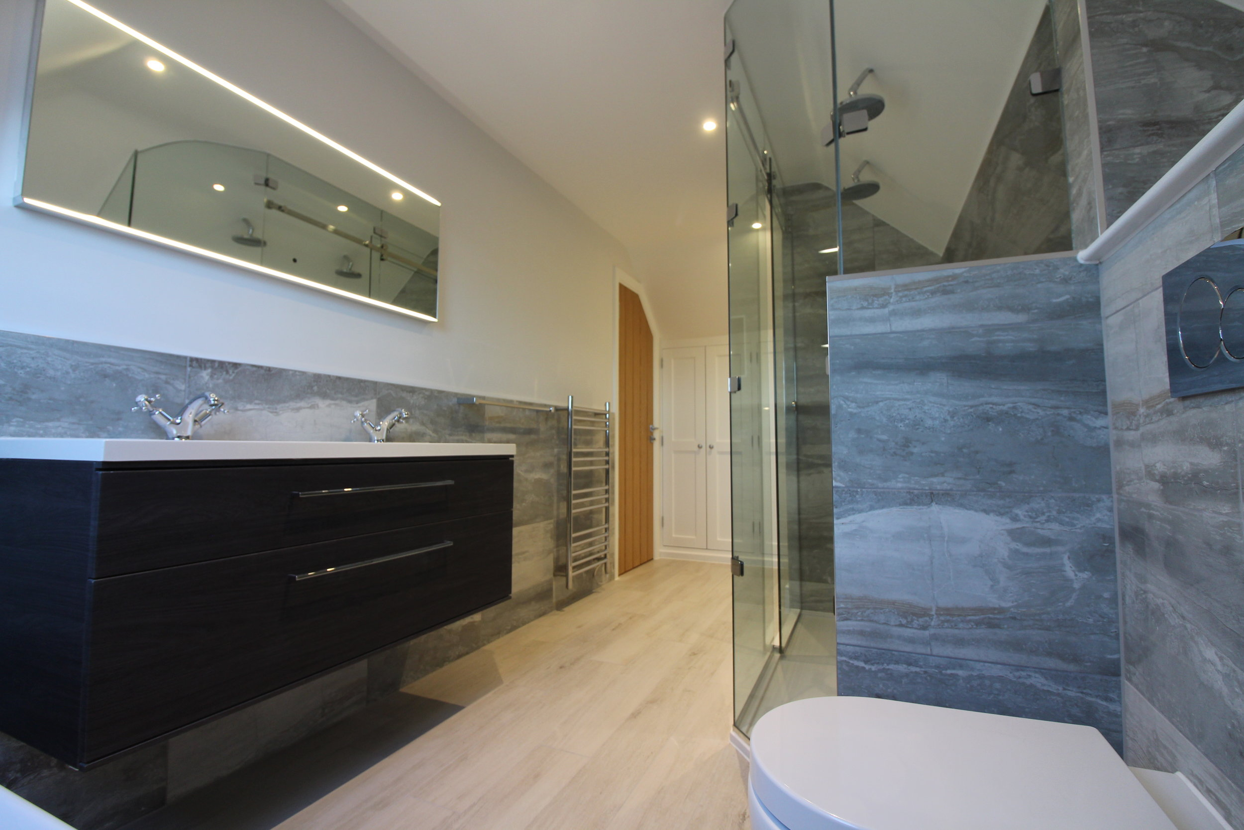 The bathroom is simple, light and sleek, with a wall hung 'his and hers' basin unit.