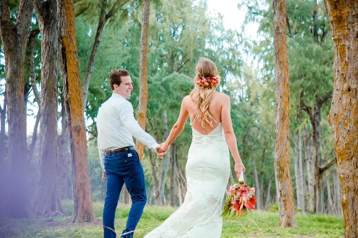 bride and groom walking in forest hawaii destination wedding