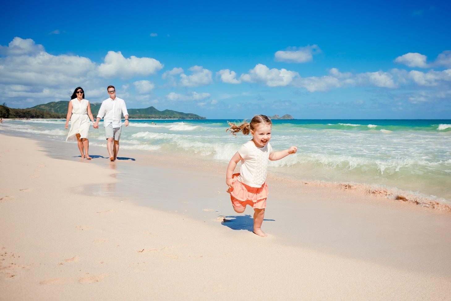 family kids running down hawaii beach sand waves