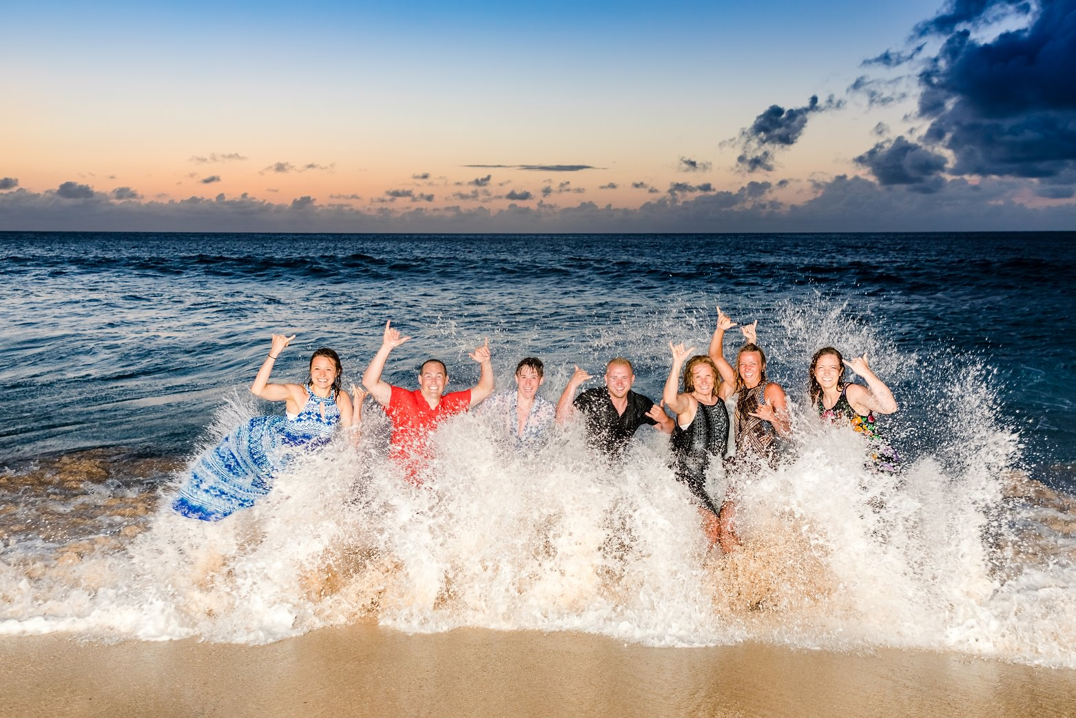 family portrait in ocean wave at sunset beach oahu