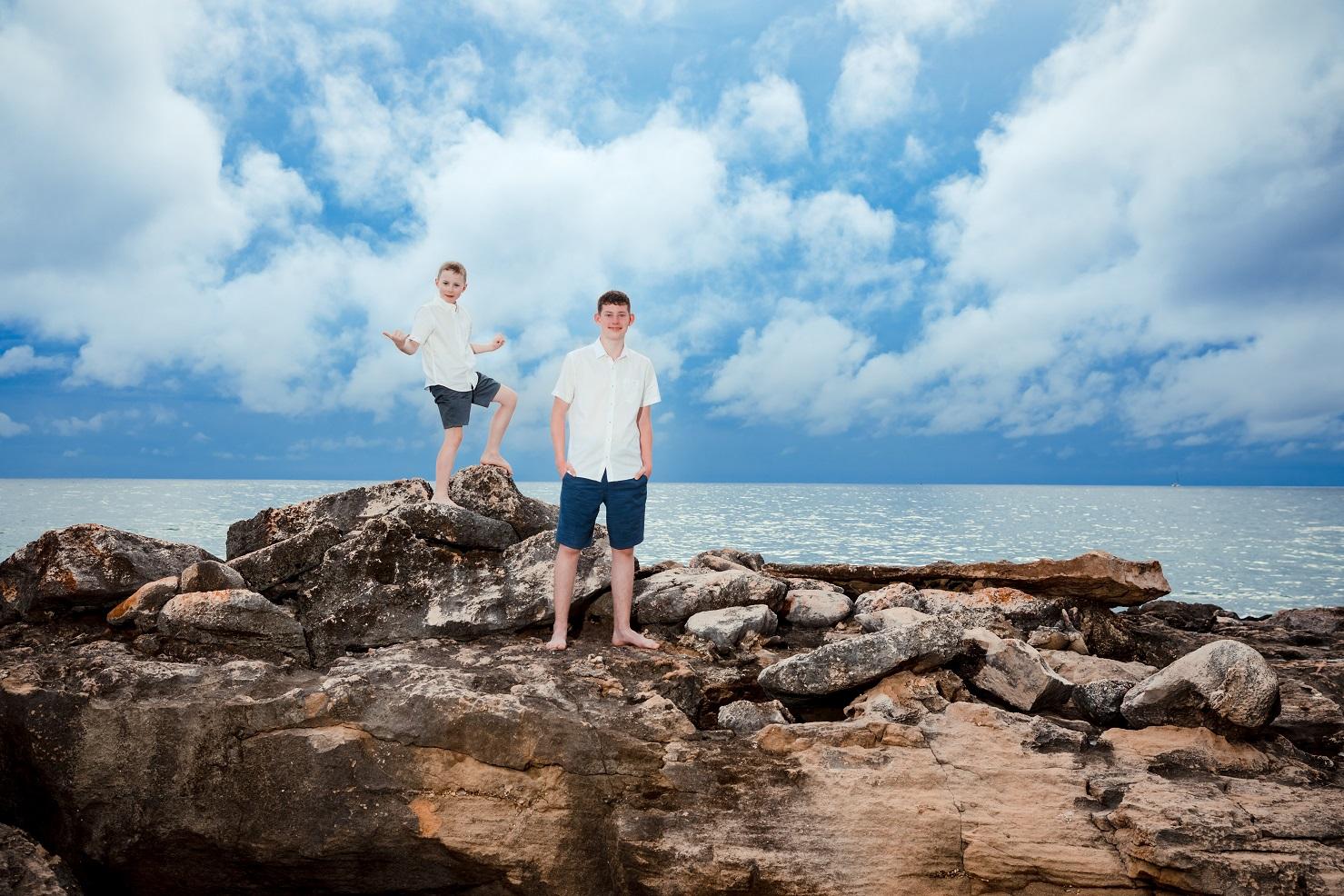 two boys on a rock sunset beach oahu hawaii