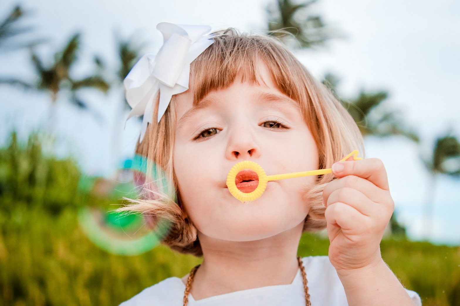 girl blowing bubbles on the beach