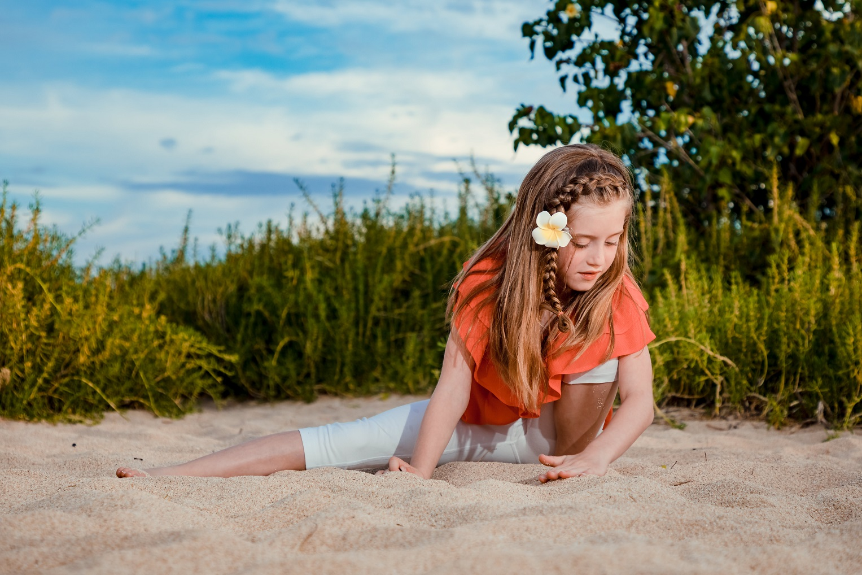 girl doing gymnastic splits on oahu beach