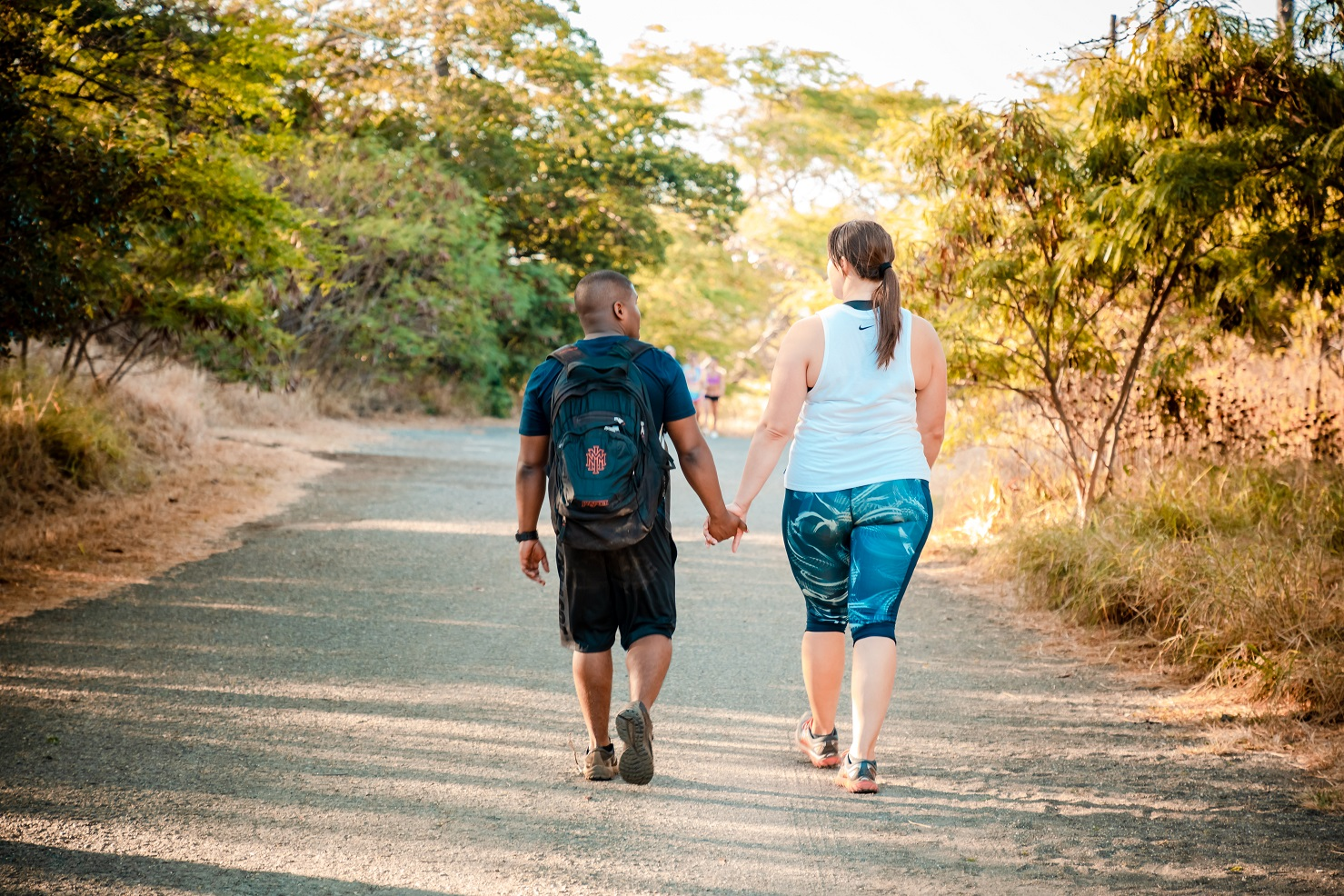 engaged couple walking hand in hand on hawaii road