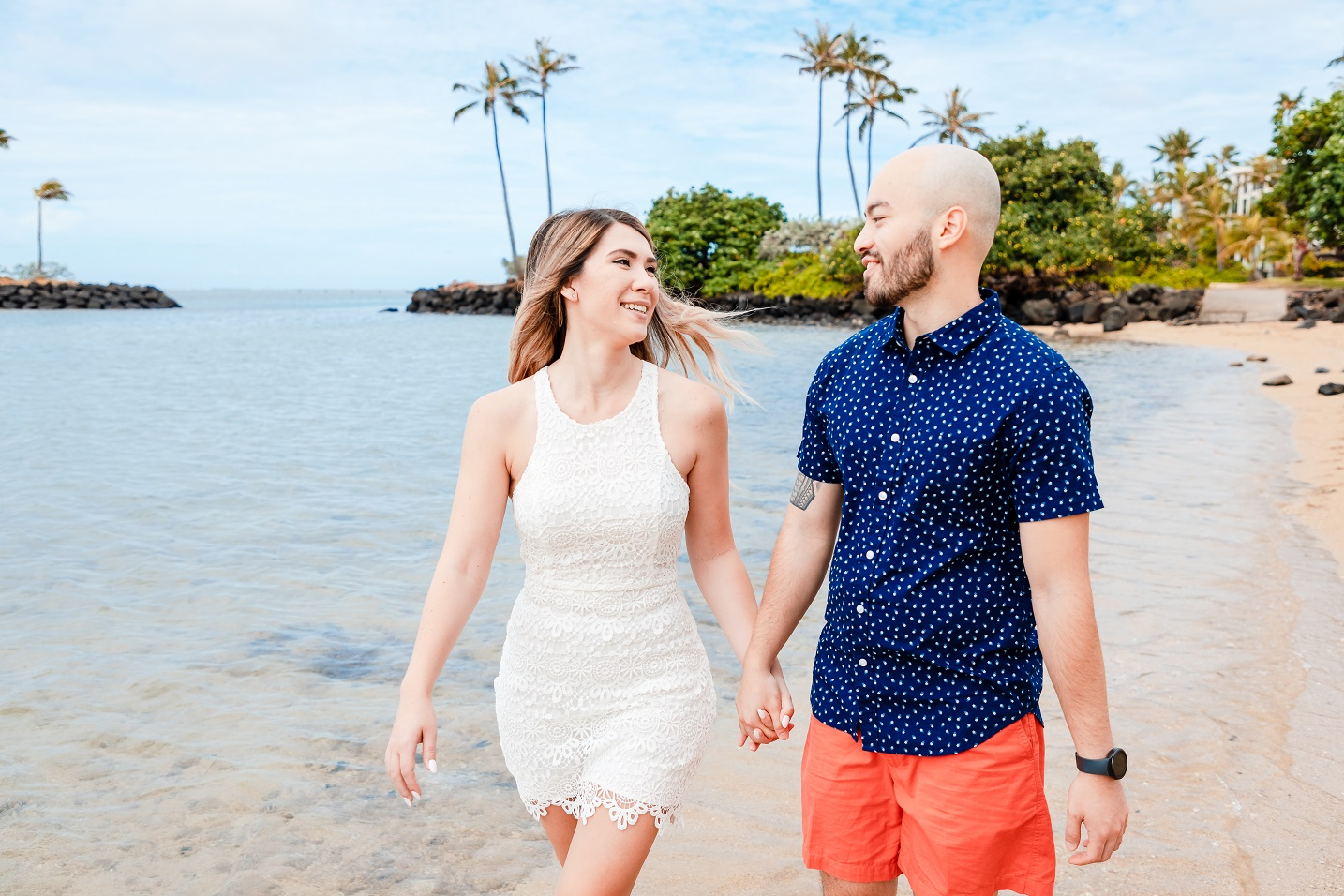 engaged couple walking on beach portrait