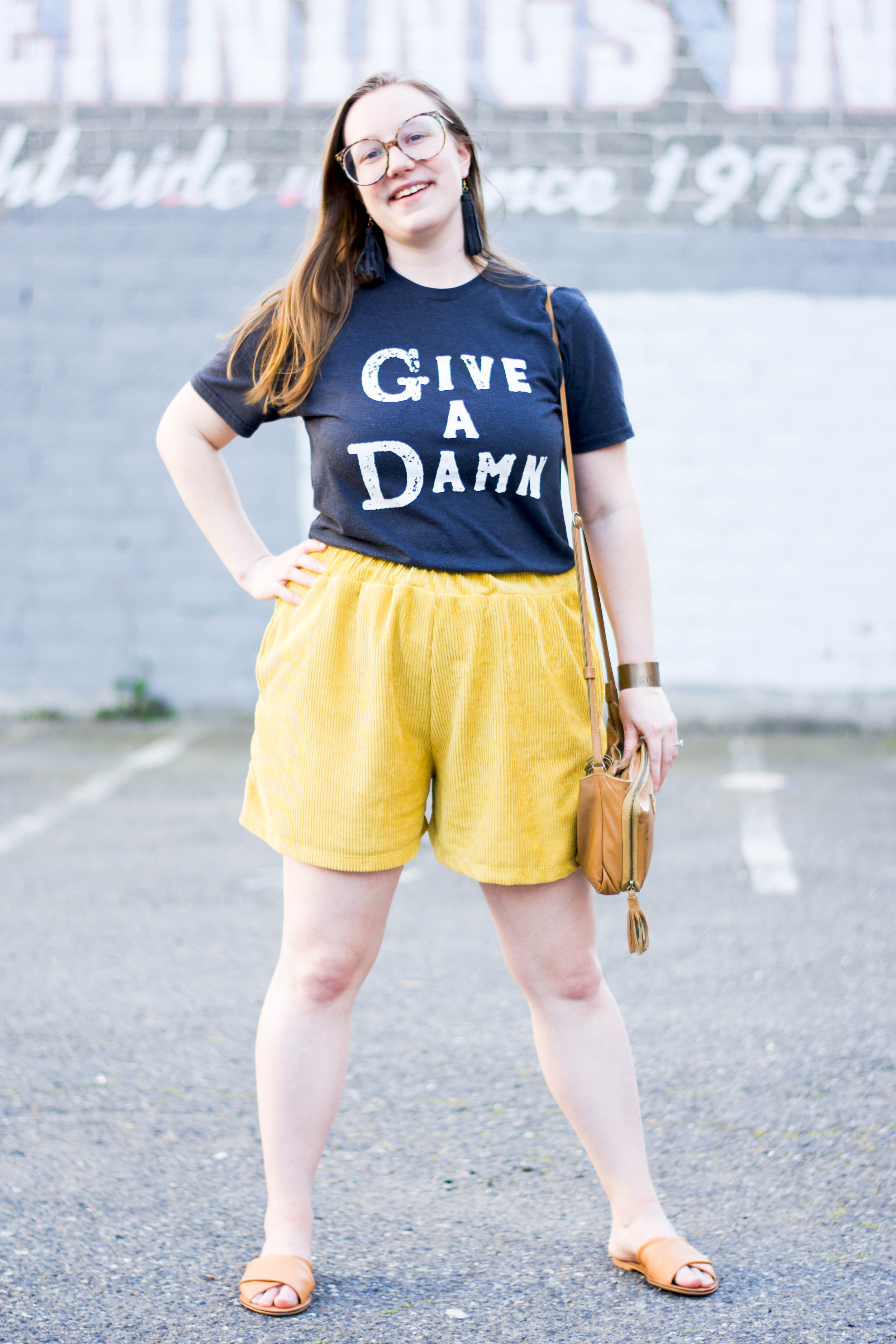 Sustainably styled in:  Give a Damn tee  from  Give a Damn Goods ,  Zero Waste Shorts  from  Tonlé  + upcycled leather earrings from Give a Damn Goods + Medium Cuff from  BRANDED Collective.