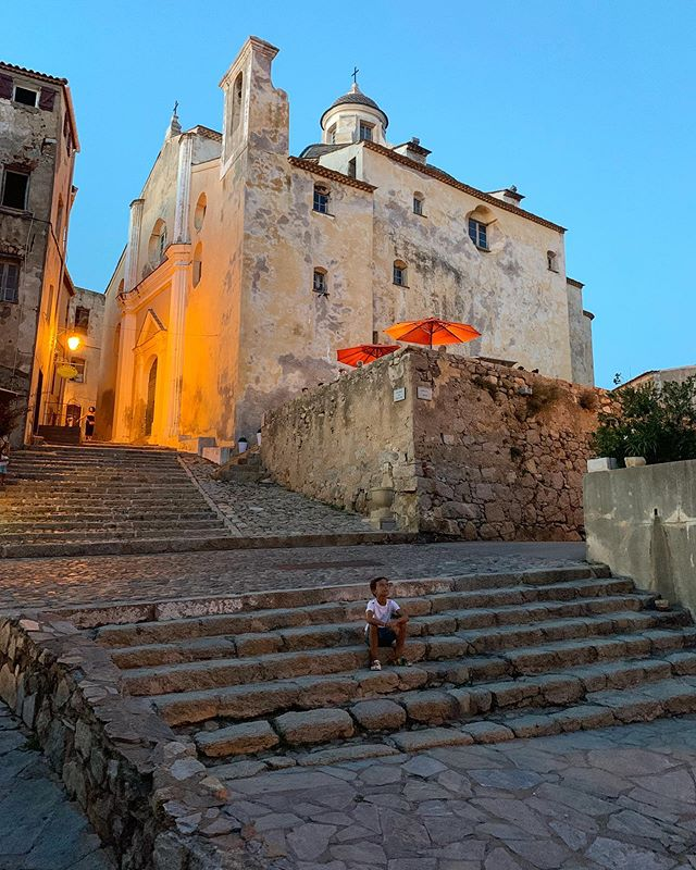 My little guy checking out the sunset at the top of the historic Citadelle de Calvi. The oldest part of this fortress was built in 1278. It is so fascinating to explore a city so old but still in full swing. We had dinner up near the orange umbrellas and the citadel is full of cafes, shops and people that still live there. Just so full of original beauty. Surrounding the #citadel is the most stunning beach. Such an amazing and special place to visit 🇫🇷 #france #corsica #calvi #corse #french #travel #original #beauty  #familytravel #memories #travelphotography #familytime #explore #sunset #visitcorsica