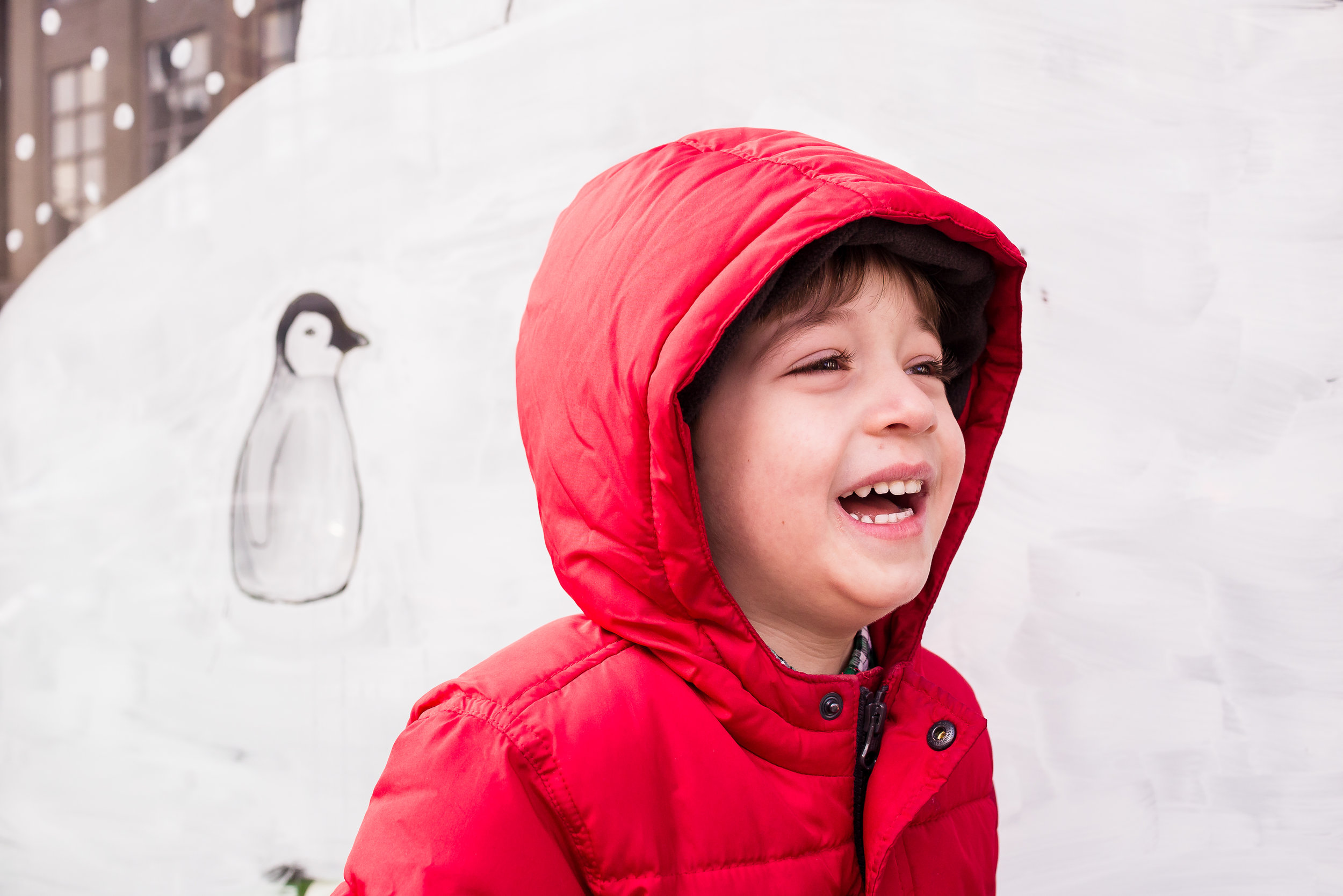 boy laughing in red coat