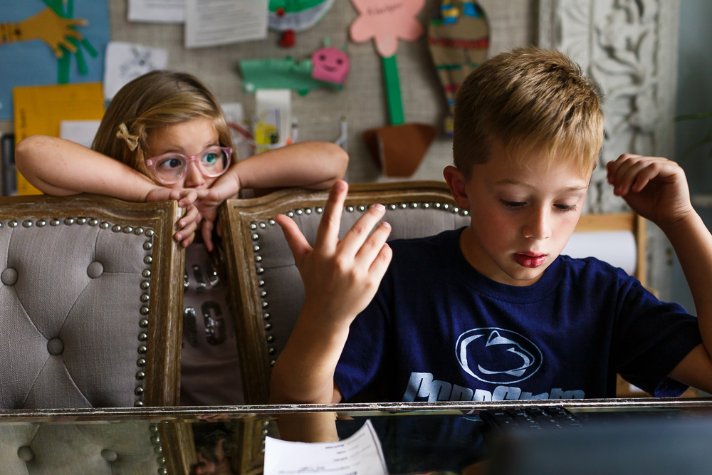 Boy struggling to do homework while his sister watches.