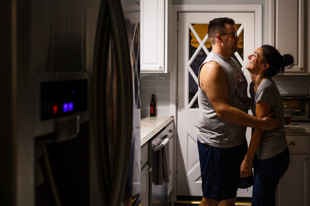 Husband and wife being lovey in the kitchen after the kids go to sleep.