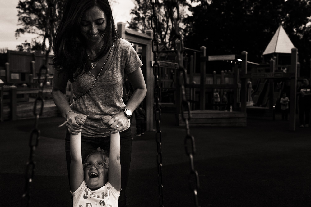 mom pulling kid off of the tire swing at the playground