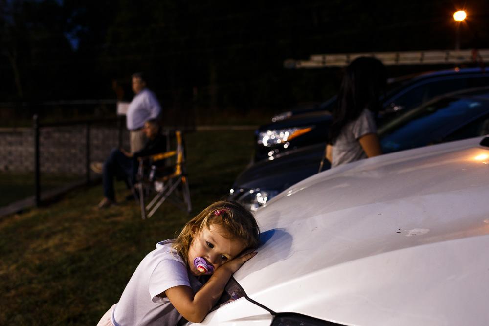 Little kid resting against white car.