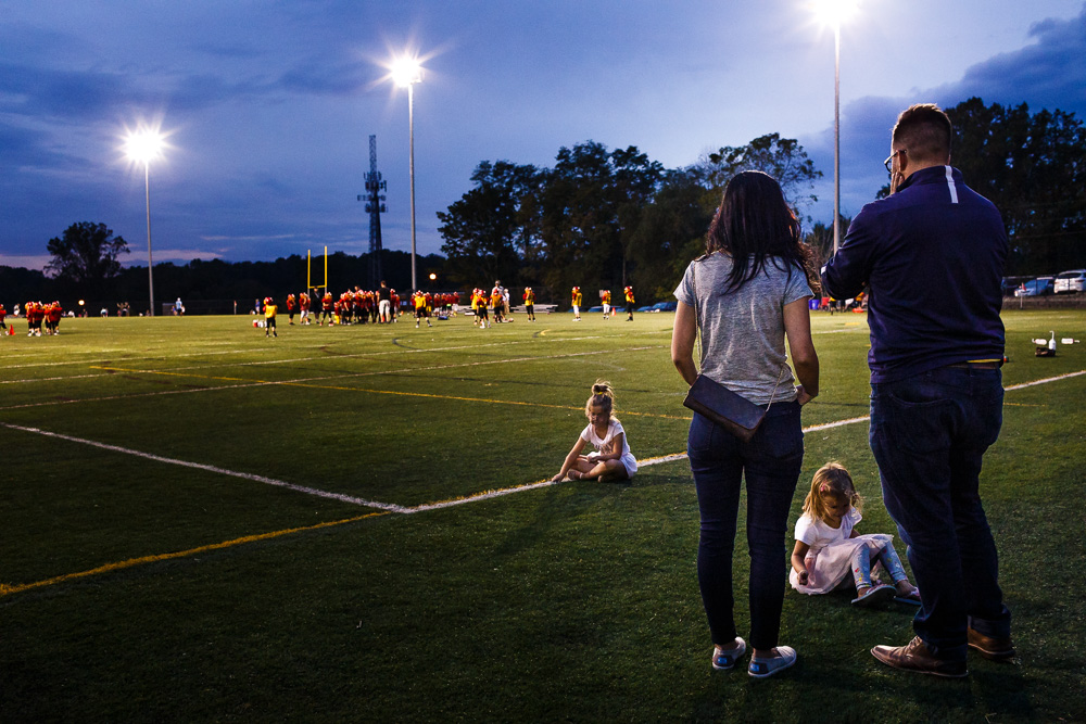 Family watching sons football practice