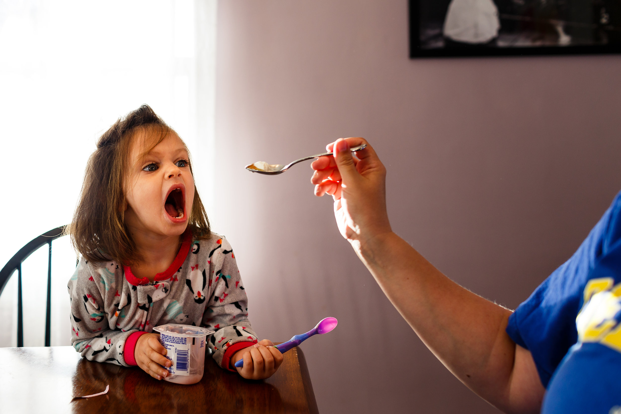 girl with mouth open wide for yogurt