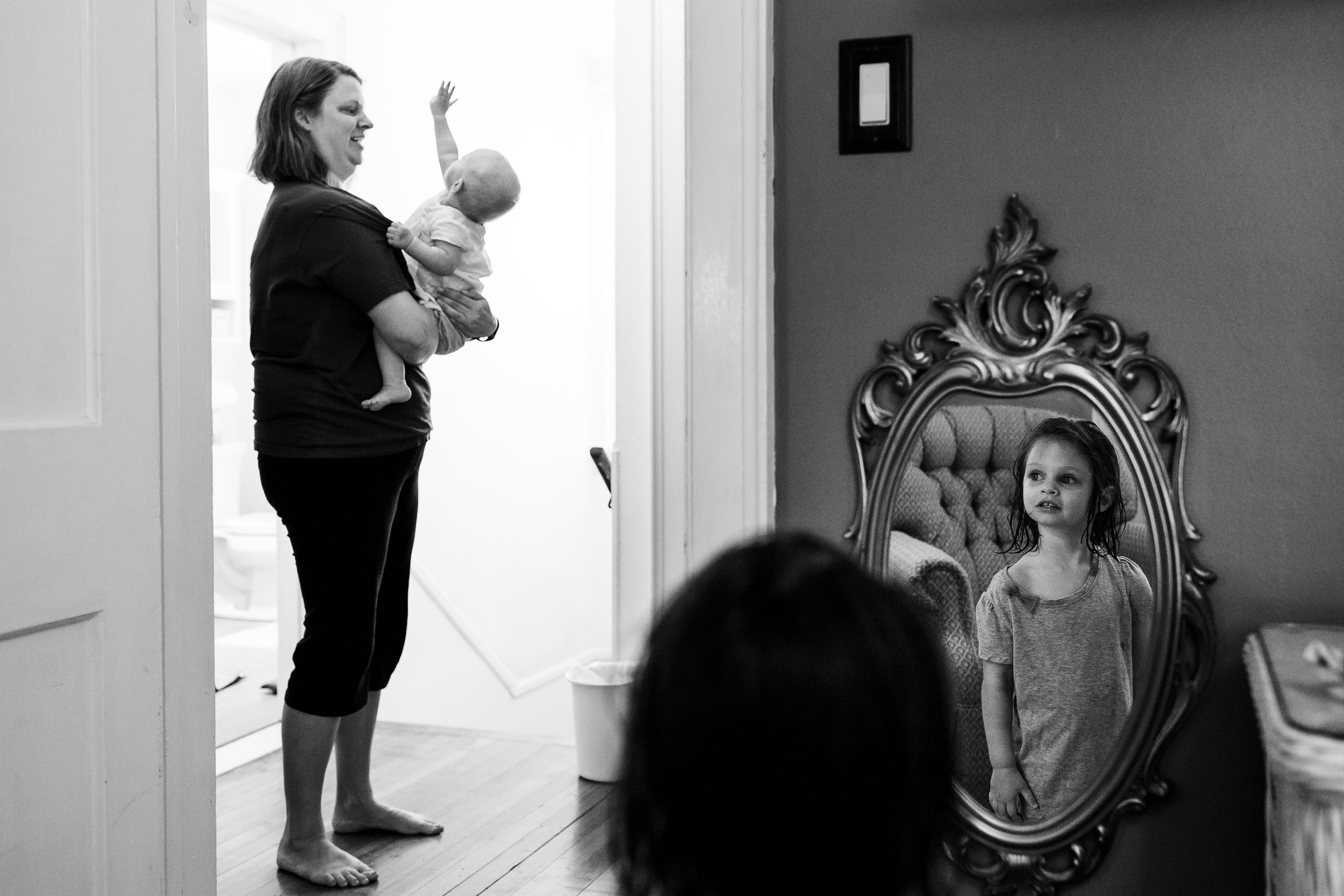 girl looking at herself in mirror and looking at mom