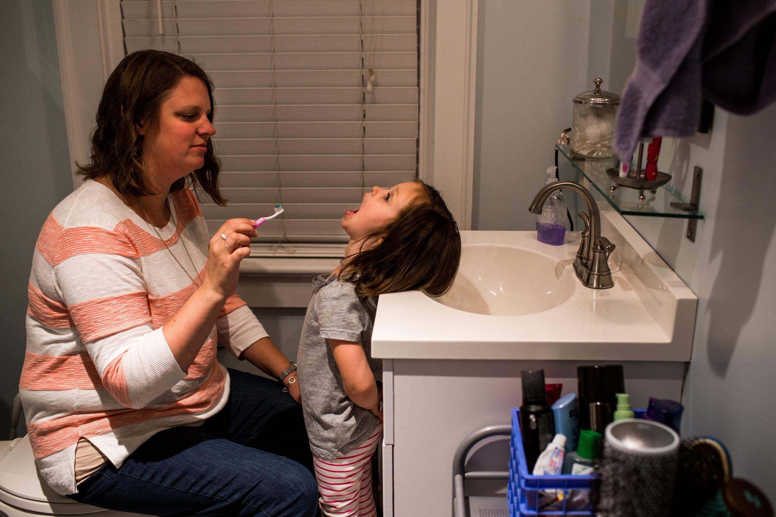 mom brushing daughters teeth