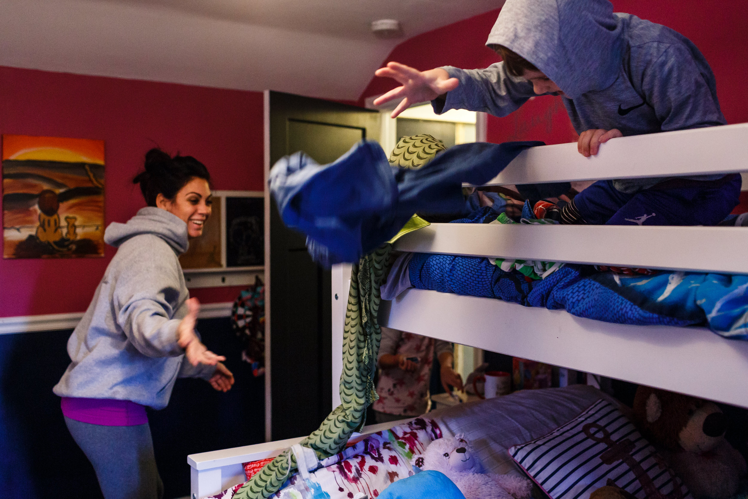 mom throwing clothes up to son on bunk bed