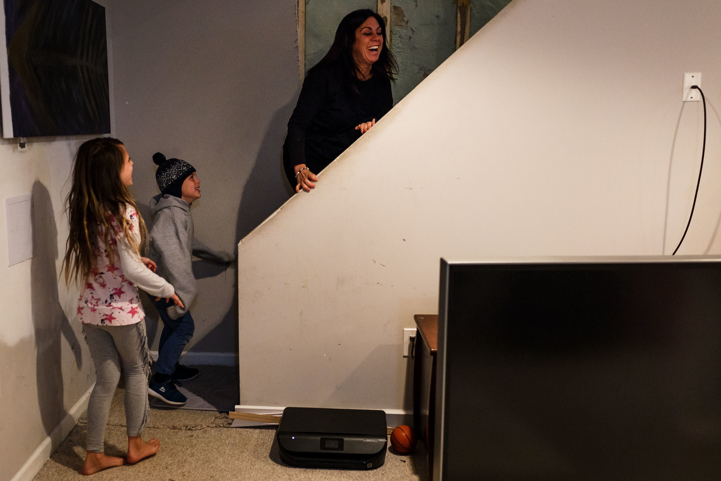 Mom laughing at kids on the staircase