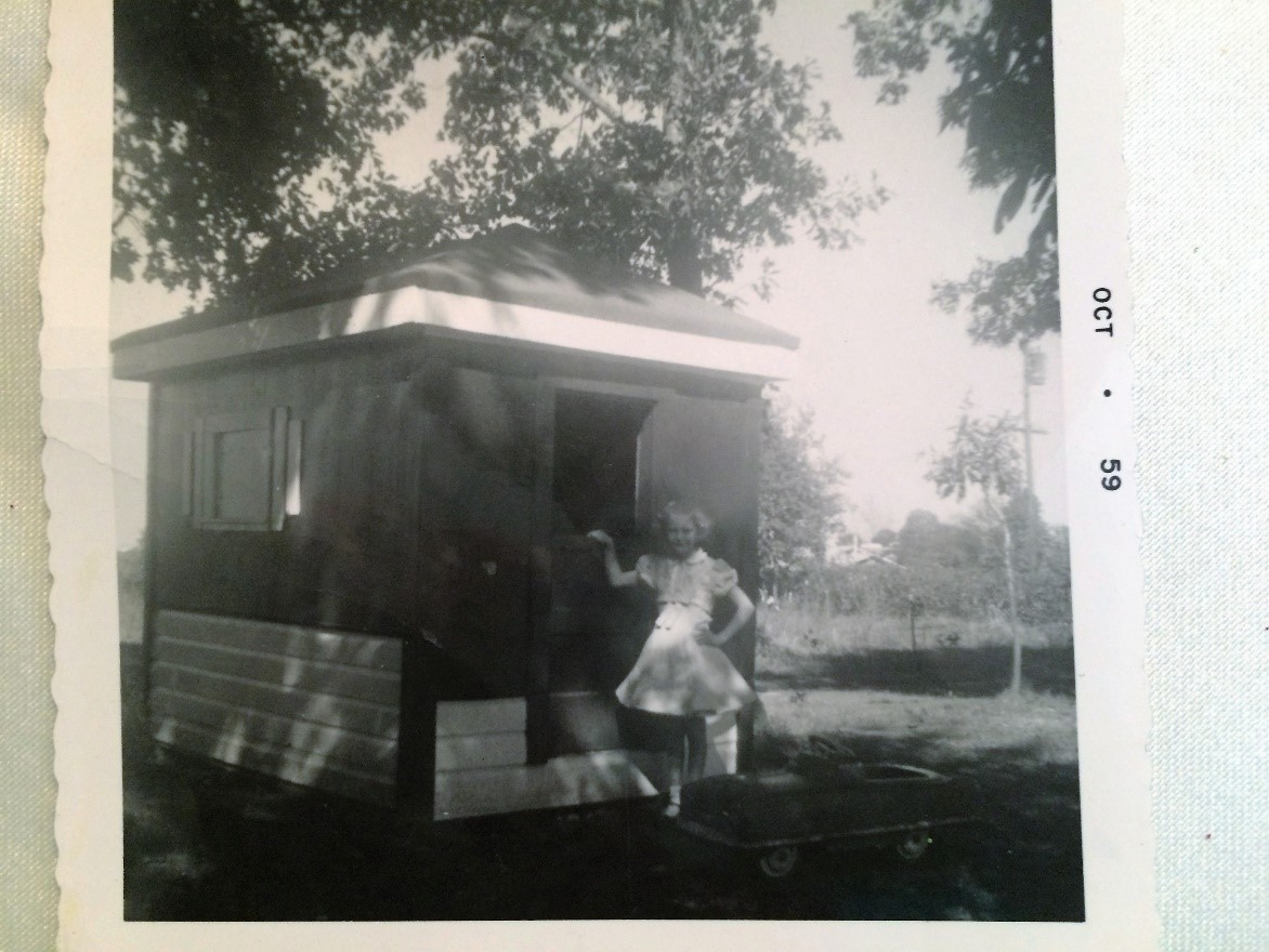Linda at eight years old in front of the playhouse Mom built me