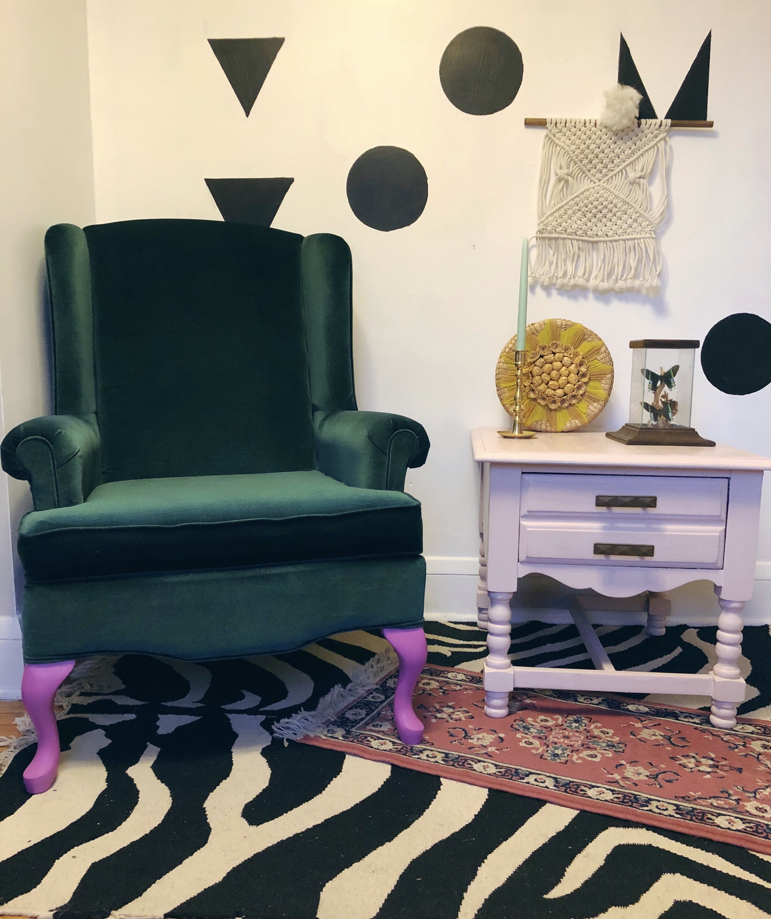Shop the look:  Bold Boho Wingback Chair ,  Dark Blush Persian Style Rug ,  Blush Pink End Table ,  Brass Candlesticks ,  Starbust Wicker Basket,   Vintage Butterfly Terrarium  and  Macrame Wall Hanging .