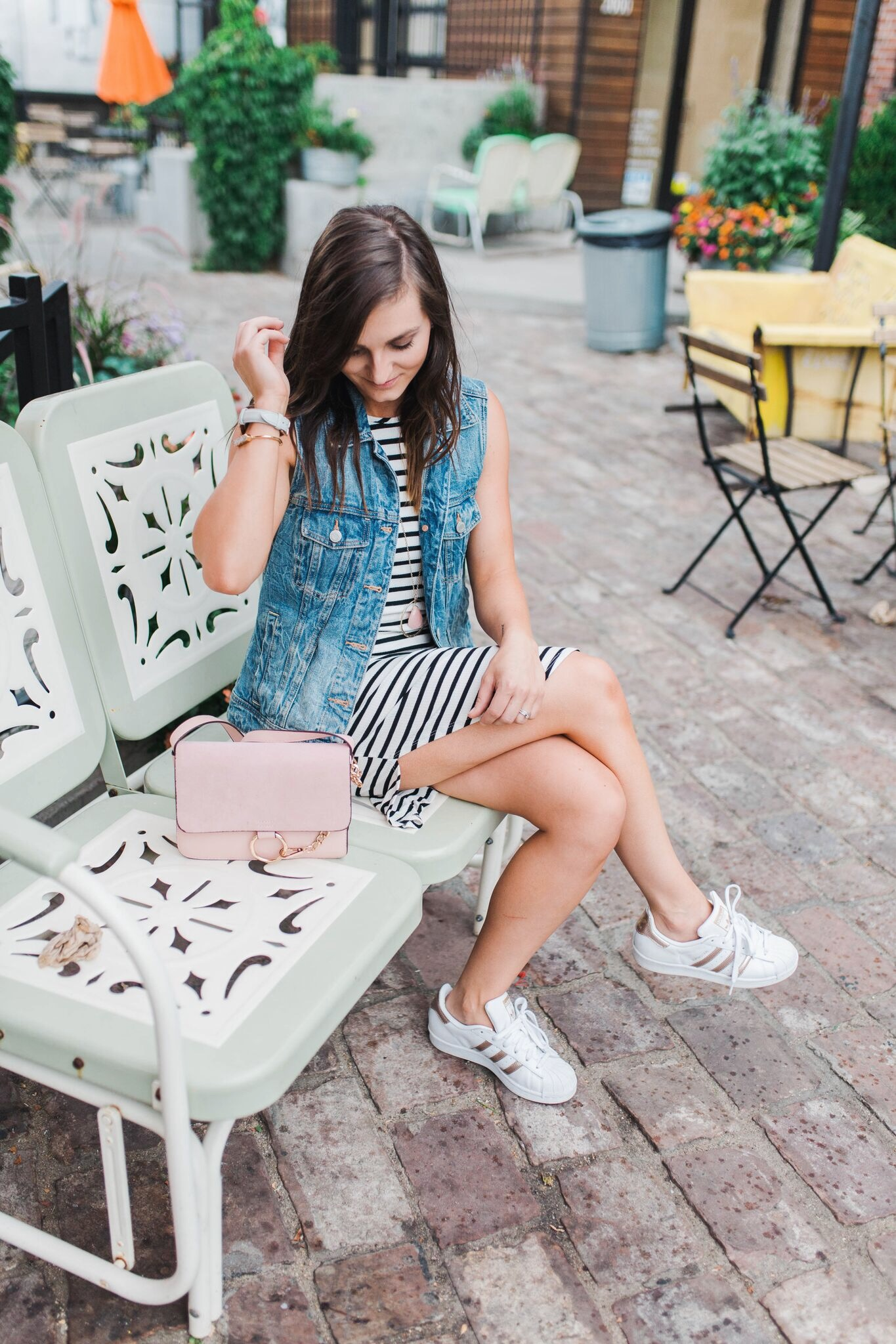 "<img src = ""how-to-style-sneakers.jpg"" alt = fashion-blogger-sitting-on-a-bench-wearing-a-black-and-white-striped-dress-denim-vest-and-rose-gold-adidas-superstars>"