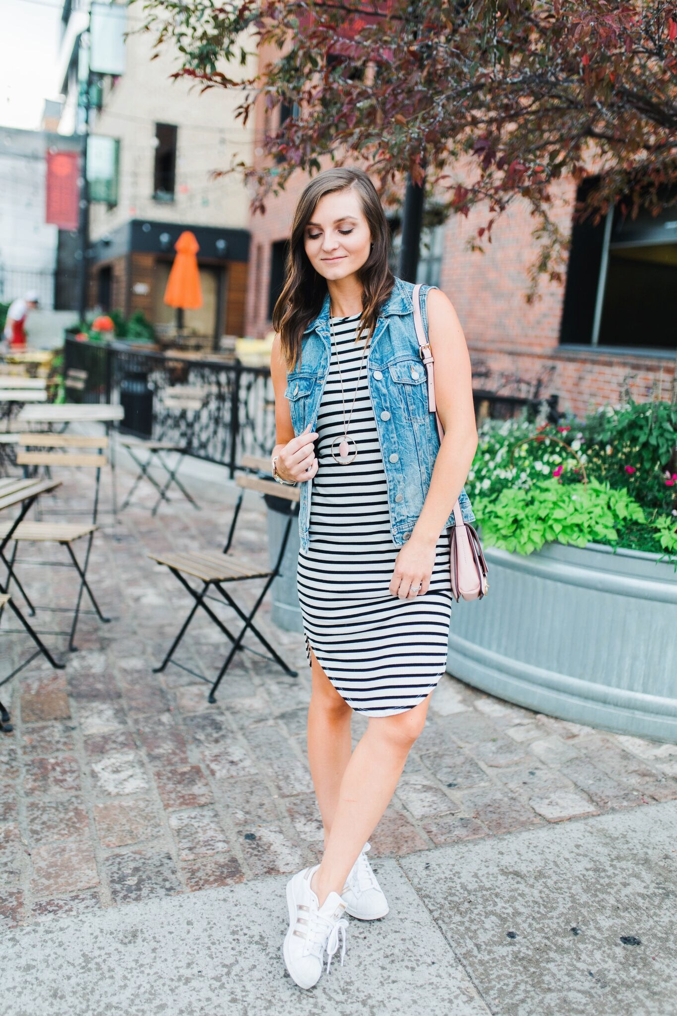 "<img src = ""how-to-style-sneakers.jpg"" alt = fashion-blogger-in-downtown-denver-wearing-a-black-and-white-striped-dress-denim-vest-rose-gold-adidas-superstars-and-pink-chloe-faye-dupe>"