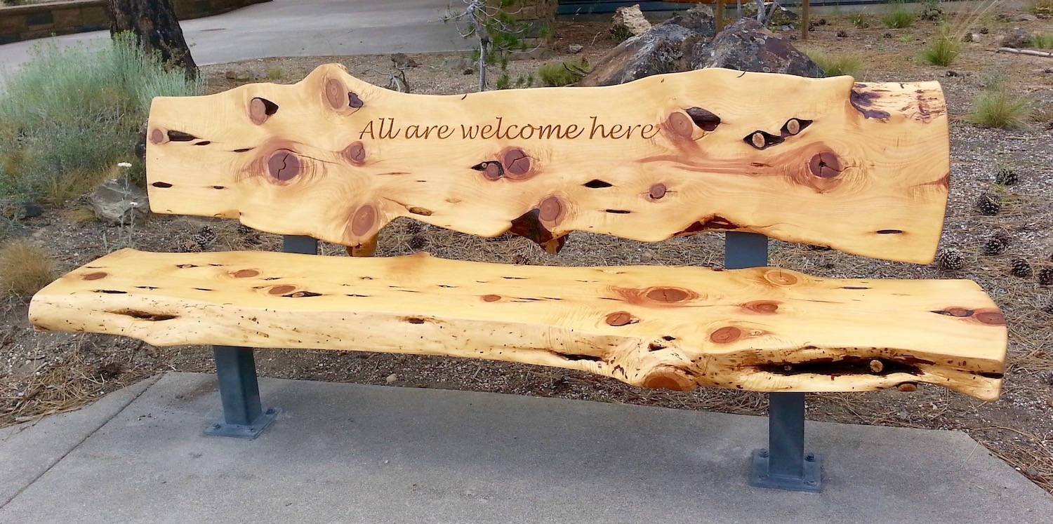 "Photo of the ""All are welcome here"" bench at the entrance."