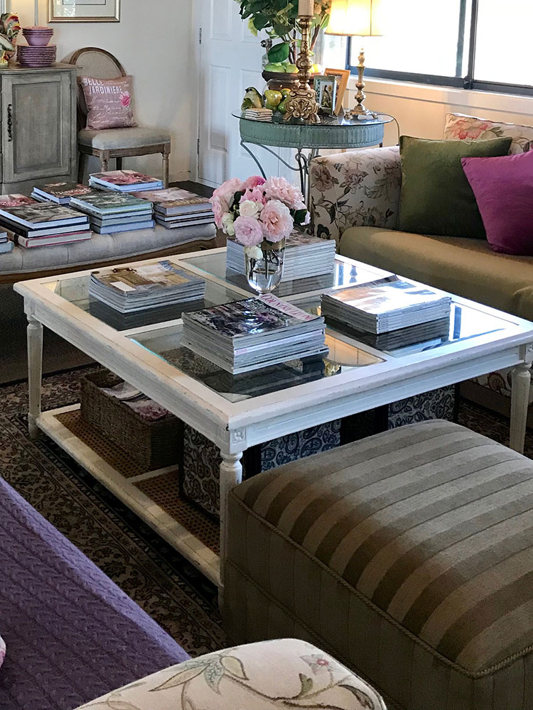 A glass-top coffee table with a cane bottom in white lime-wash wood is a light and airy touch for the room. Its open style still provides excellent storage for boxes and lots of favourite magazines.