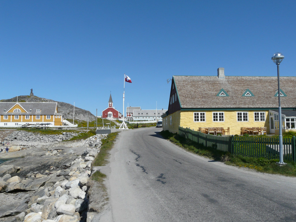 Hans Egede House (right), built in 1728.  Statue of the eponymous missionary on top of the hill on the left