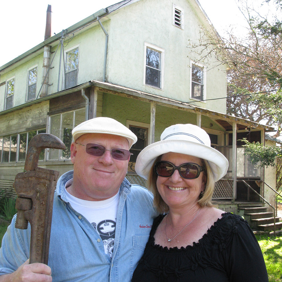 Sue and Alan Cooper in front of their 1879 farmhouse, pre-renovation.